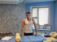 Массажист Илья рядом с массажным столом