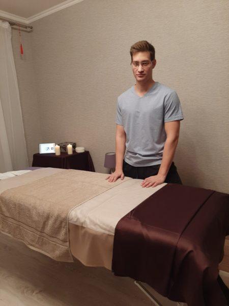 Массажист Григорий рядом с массажным столом
